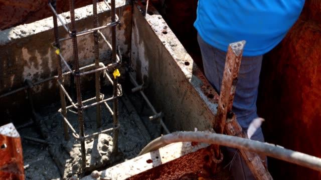 vídeos y material grabado en eventos de stock de trabajadores profesionales de la industria de la construcción asiática que trabajan como un trabajo en equipo con la unidad vertiendo hormigón en el pie. construcción de casas pequeñas - aleación