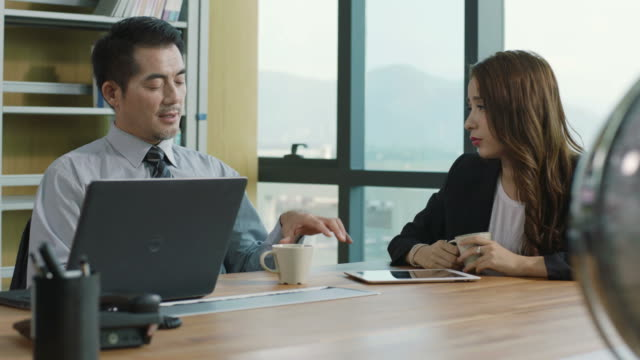 asian corporate executive discussing business in office video