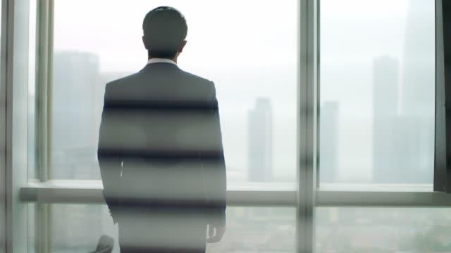 esecutivo aziendale asiatico in piedi di fronte al pensiero finestra - guardare il paesaggio video stock e b–roll