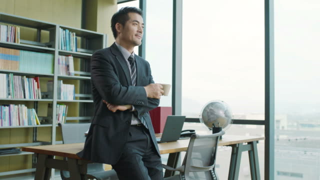 asian corporate executive thinking in office asian businessman leaning against desk holding a of coffee while thinking in office. east asian culture stock videos & royalty-free footage