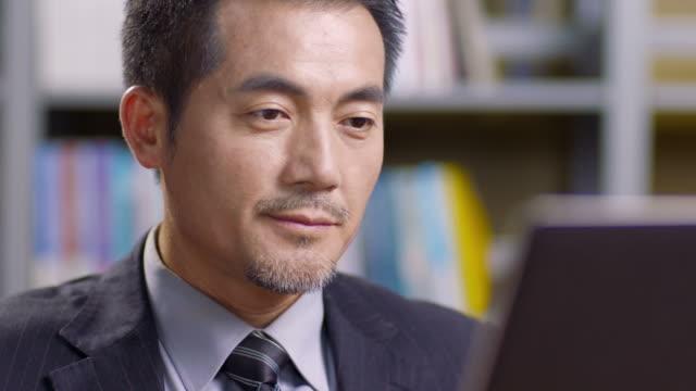 asian corporate executive working in office - cultura orientale video stock e b–roll