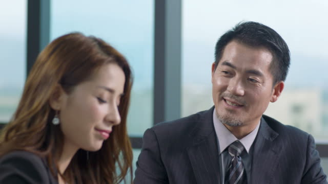 asian corporate executives chatting in office video