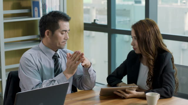 asian corporate executives discussing business in office video