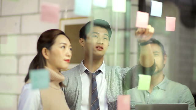 asian corporate executives discussing business strategies using adhesive notes video
