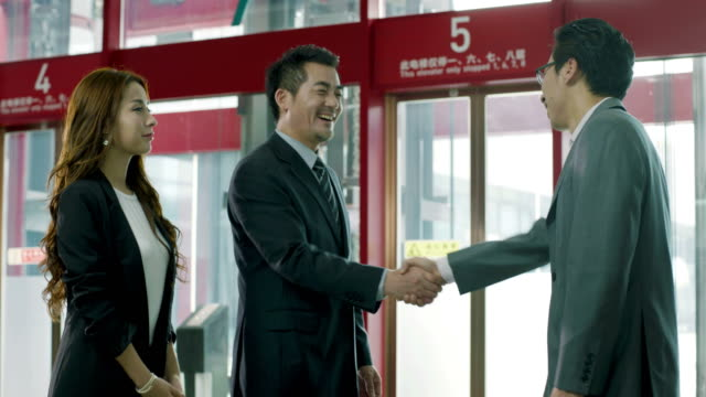 asian corporate executives greeting business visitor asian corporate executive and assistant greeting and shaking hands with visiting client in company lobby. chinese culture stock videos & royalty-free footage