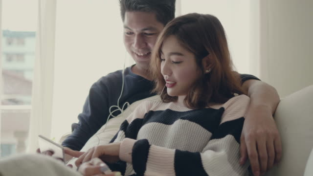 asian couple at home listening to music on smartphone - christmas movie video stock e b–roll