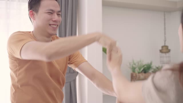 asian couple dance while listen to music in living room at home, sweet couple enjoy love moment while lying on the sofa when relax at home. lifestyle couple relax at home concept. - coppia eterosessuale video stock e b–roll