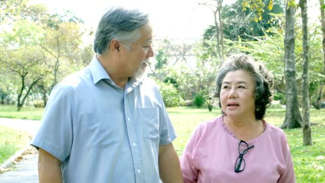 vídeos y material grabado en eventos de stock de pareja asiática ancianos relajación en el parque juntos. concepto de estilo de vida de las personas - casados