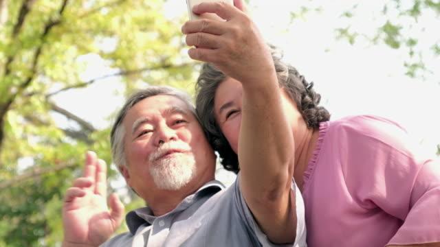 アジア高齢者の人々 の携帯電話を使用して skype 経由で話をカップル - シニア点の映像素材/bロール