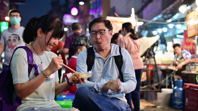 4K Asian couple enjoy eating on the street food at Bangkok Chinatown with traffic