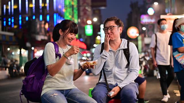 4K Asian couple enjoy eating on the street food with traffic at Yaowarat road, Bangkok
