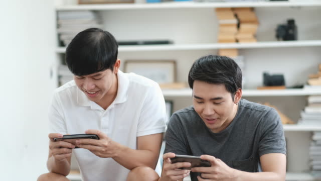 Asian couple gay play mobile game together in study room and they look happy