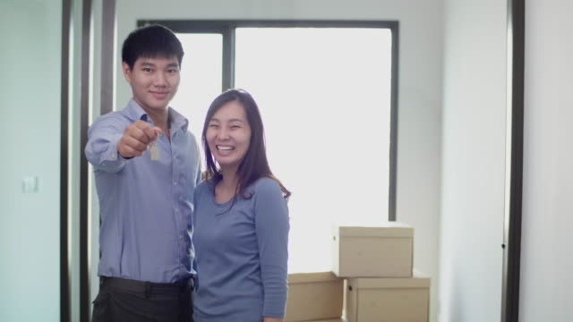 vídeos de stock e filmes b-roll de asian couple holding key house,  showing keys buying new apartment looking at camera - buy a house key
