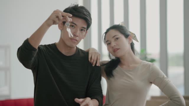 아시아 부부는 자신의 새로운 집의 열쇠를 들고 - home 스톡 비디오 및 b-롤 화면
