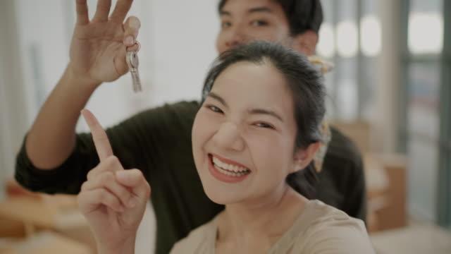 asiatisches paar hält die schlüssel ihres neuen hauses - hausschlüssel stock-videos und b-roll-filmmaterial