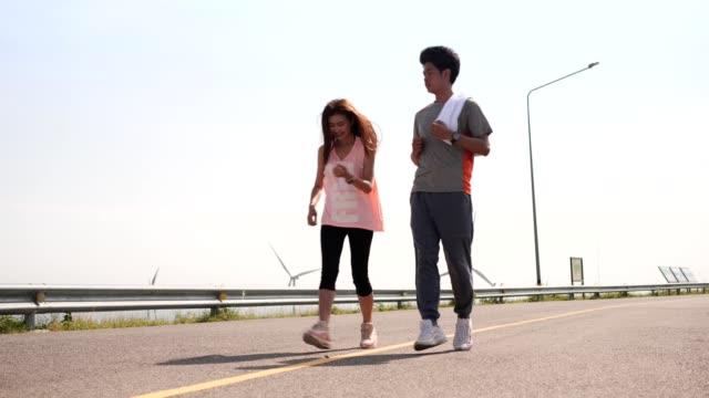 アジア人カップル早朝の風力発電場でジョギングやランニング。健全なコンセプト。 - 人の筋肉点の映像素材/bロール