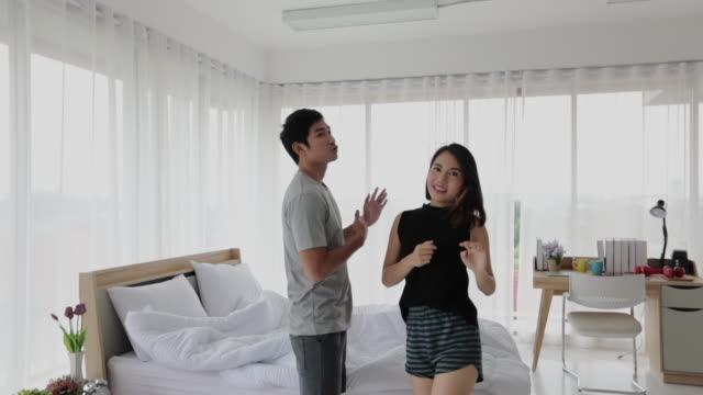 Asian couple lovers listening to music and singing dancing on his bedroom and happy on relax time video