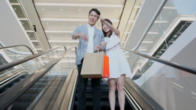 vídeos de stock, filmes e b-roll de casal asiático em uma escada rolante em um shopping center - shopping center
