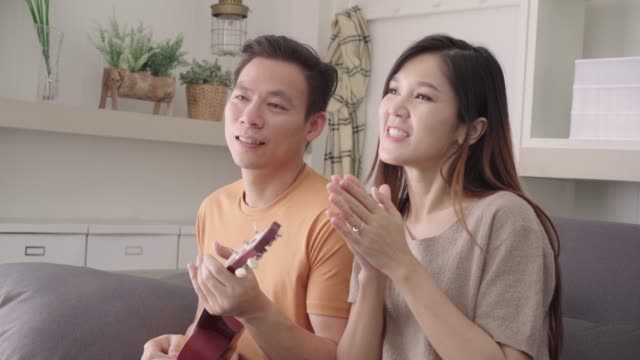 asian couple playing guitar and singing together in living room at home, sweet couple enjoy love moment while lying on the sofa when relax at home. lifestyle couple relax at home concept. - coppia eterosessuale video stock e b–roll