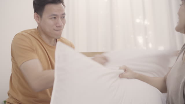 coppia asiatica che gioca a pillow fight sul letto in camera da letto, moglie e marito si godono un momento divertente mentre sono sdraiati sul letto a casa. la coppia si rilassa godersi il momento dell'amore a casa concetto. - coppia eterosessuale video stock e b–roll