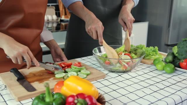 vídeos y material grabado en eventos de stock de pareja asiática preparando ensalada saludable con juntos en la cocina. - cáliz objeto religioso