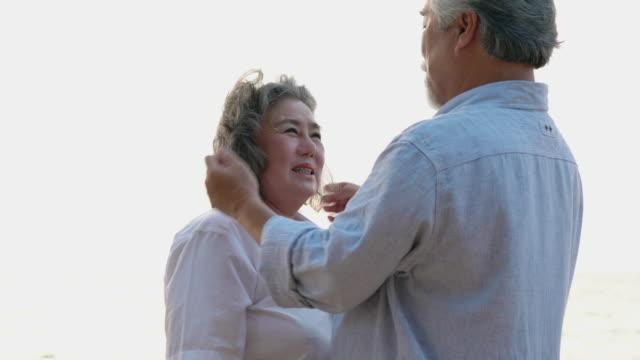 アジアのカップルシニアは一緒に抱きしめ、ビーチでロマンチックな夏を感動。幸せな家族のコンセプト, 退職後, 結婚記念日, メンタルヘルスと夏の旅行. - 老夫婦点の映像素材/bロール