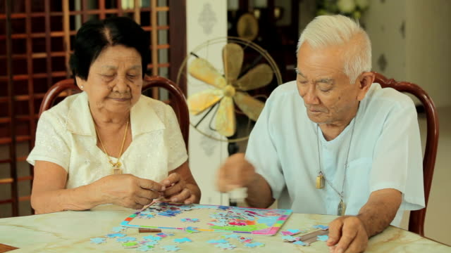 Asian couple senior playing with a jigsaw puzzle at home video