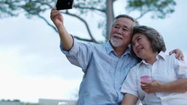 アジアのカップルシニアシッティング記念日と一緒にビーチでスマートフォンで写真撮り。幸せな家族のコンセプト, 退職後, 祝賀周年記念結婚と夏の旅行. - 老夫婦点の映像素材/bロール