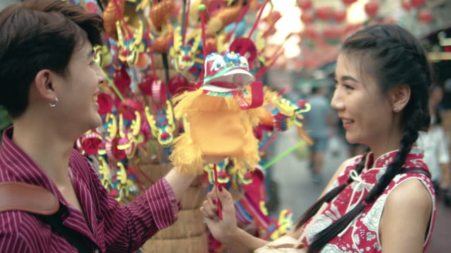Asian couple shopping at street market in Chinatown Bangkok, Thailand. Chinese tourist buying vintage dragon toy in chinese new year festival at Yaowarat Road. Bangkok, Thailand;. souvenir stock videos & royalty-free footage