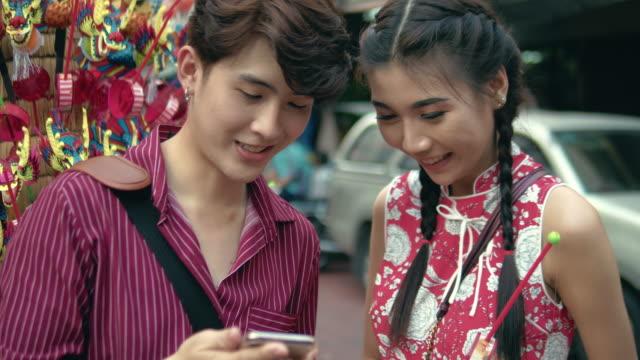 Asian couple shopping at street market in Chinatown Bangkok, Thailand.
