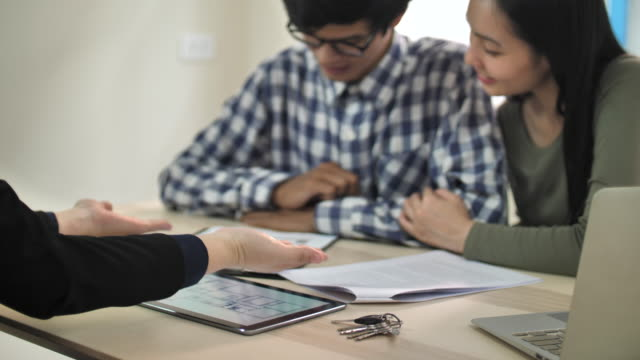 Asian Couple sign mortgage contract and handshaking realtor at meeting with estate agent