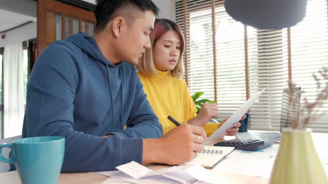 Asian couple sitting at table in kitchen calculate home budget with paper bill and laptop in new house.
