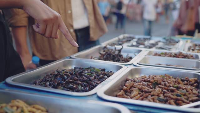 カオサンロードで火の昆虫を楽しむアジアのカップルの観光客。バンコク - 異国情緒点の映像素材/bロール