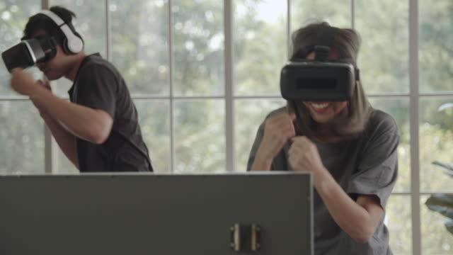 Couples asiatiques utilisant des lunettes 3-D dans le jeu de vr de boxe à la maison - Vidéo