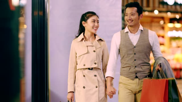 asian couple walking in shopping mall happy asian couple shoppers walking in shopping mall looking into shop window department store stock videos & royalty-free footage