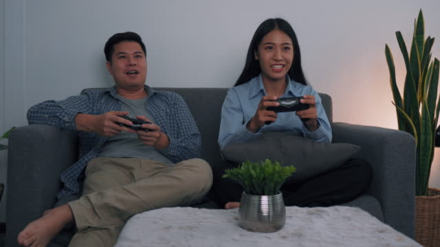Asian couples are having fun playing games in their living room at night.