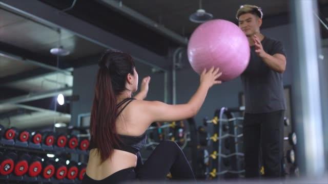 vídeos de stock, filmes e b-roll de casais asiáticos se exercitam com torção russa segurem bola de yoga metáfora fitness e exercício conceito de treino saúde estilo de vida corpo muscular e saúde para treinador auxiliar treinamento - comodidades para lazer