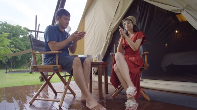 Asian Couples Resting in a tent location In a natural place