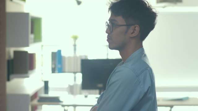 asiatische kreative mann stehen aussehende arbeitsplan auf papierplatte. junge professionelle geschäftsleute denken und schreiben informationen erinnerung über ziegel, geschäftssituation, startup in loft bürokonzept. - flussdiagramm stock-videos und b-roll-filmmaterial