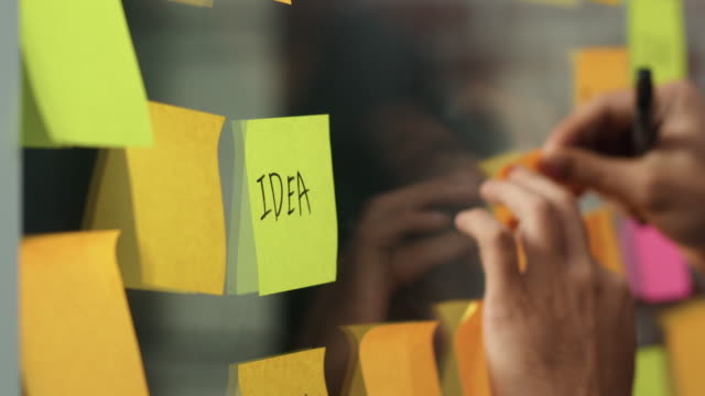 asian creative man stick a sticky note on glass board. young professional business male write information, strategy, reminder on paper, business situation, startup in loft office concept. slow motion. - post it video stock e b–roll
