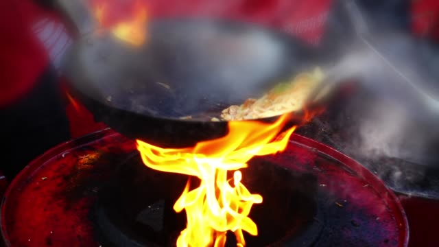 Asian cuisine. Cooking in a wok pan. Slow motion. Asian cuisine. Cooking in a wok pan. Slow motion. stir fried stock videos & royalty-free footage