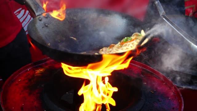 vídeos de stock e filmes b-roll de asian cuisine. cooking in a wok pan. slow motion. - cultura chinesa