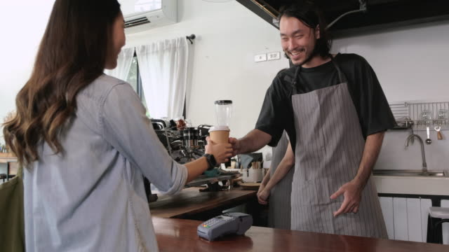 Asian customer order coffee and use smart watch pay contactless nfc on credit card machine at counter bar in cafe.small business start up.customer service concept