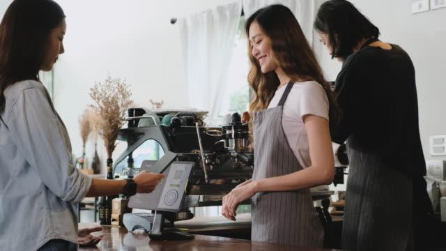 vidéos et rushes de café de commande de client asiatique de la tablette et emploient le téléphone mobile pay sans contact avec la tablette au barre de compteur dans le concept de service de café.small business. - vaisselle picto