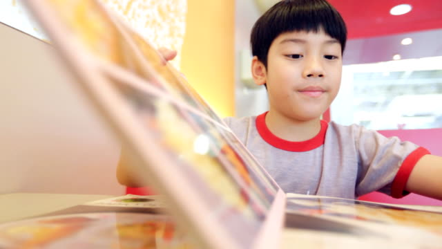 asiatisk söt pojke läsning meny bok och punkt - empty plate bildbanksvideor och videomaterial från bakom kulisserna
