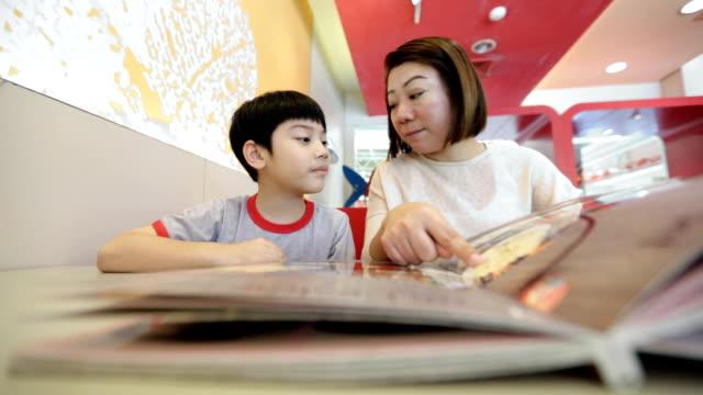 asiatiska söt pojke med mamma läsa menyn bok och punkt - empty plate bildbanksvideor och videomaterial från bakom kulisserna