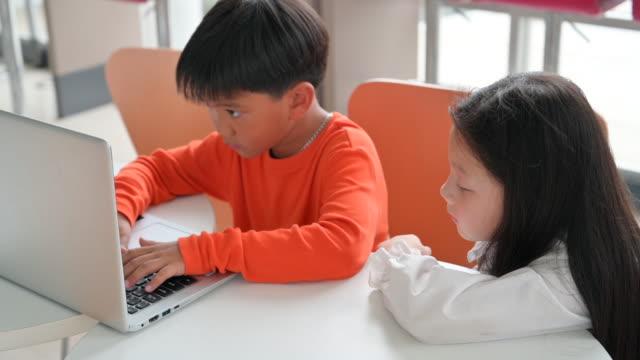 vídeos de stock, filmes e b-roll de criança asiática bonito aluno usando computador laptop juntos em sala de aula - salas de aula