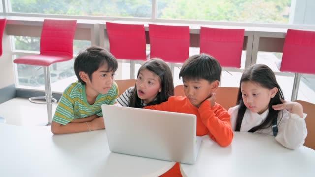 vídeos de stock, filmes e b-roll de estudante bonito asiático da criança que usa o portátil do computador junto na sala de aula - salas de aula