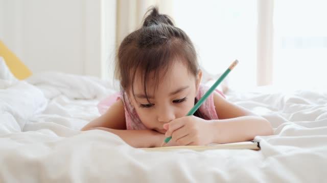 asya sevimli kız çizim ve yatak odasında yazma. - çalışma kitabı stok videoları ve detay görüntü çekimi