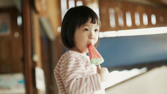 アジアのかわいい女の子はリラックスと肯定的な感情とスイカの形をしたアイスクリームを食べて、食べることを楽しむ - おやつ点の映像素材/bロール